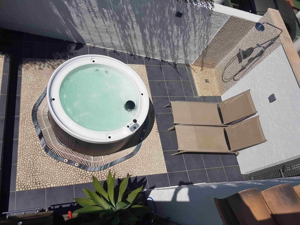 Patio avec spa, douche extérieure et transats